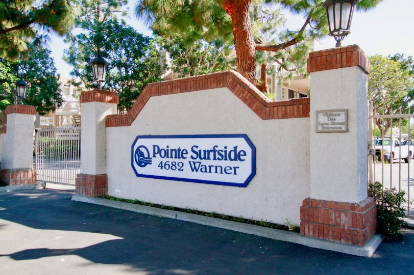 Pointe Surfside sign with gates on either side on a sunny day.