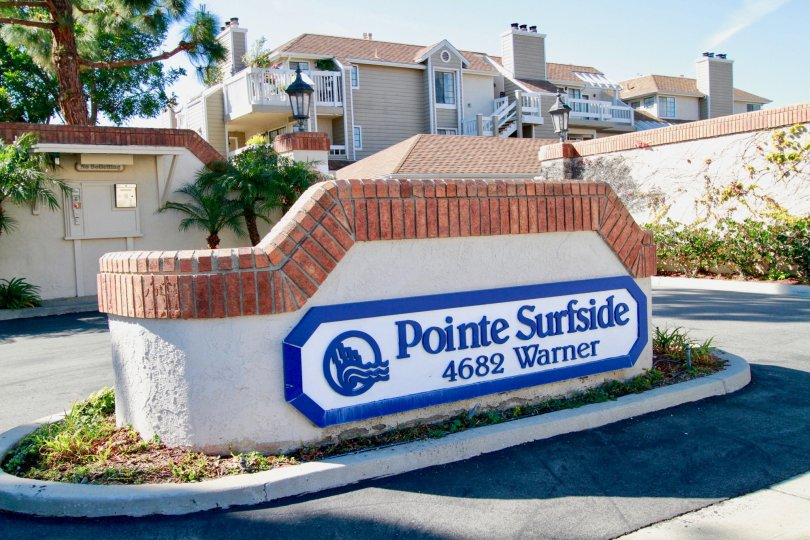 Pointe Surfside sign with a fence and roundabout on a sunny day.