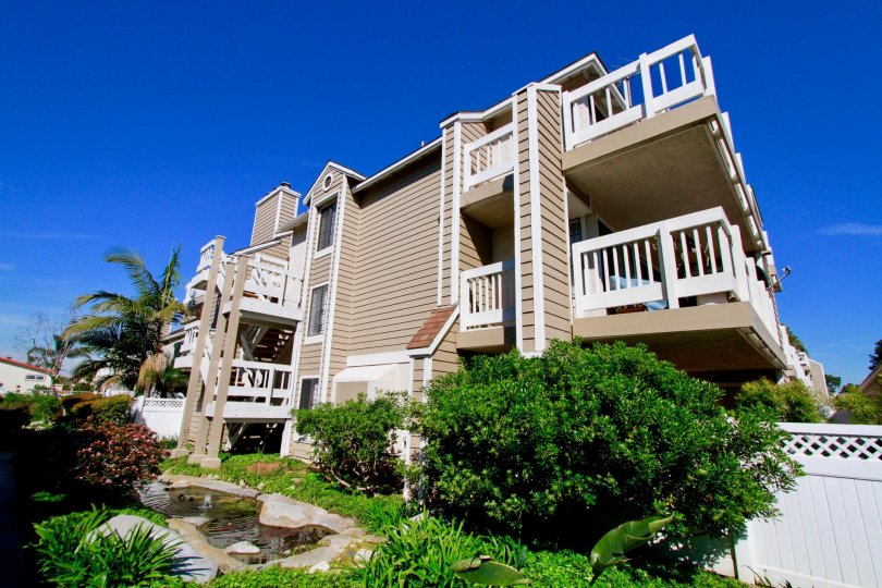 Pointe Surfside apartments with trees and balconies of a sunny day.