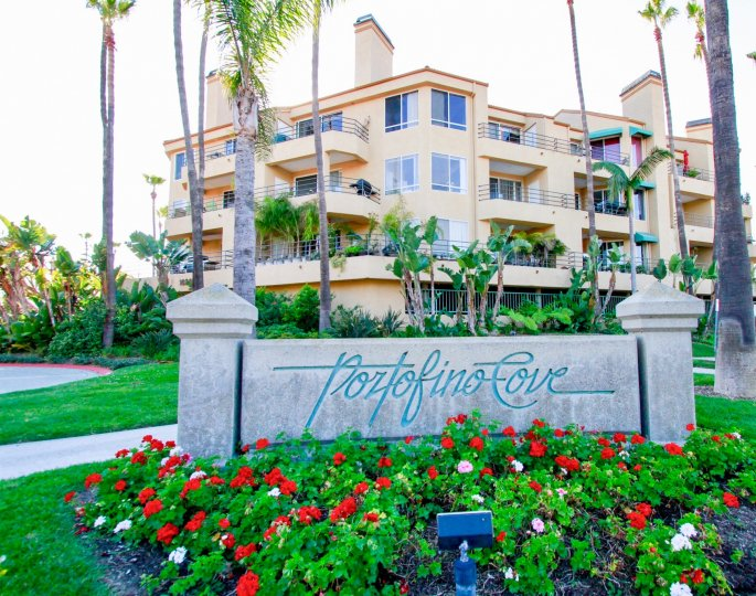Portofino Cove sign with flowers and palm trees on a sunny day.