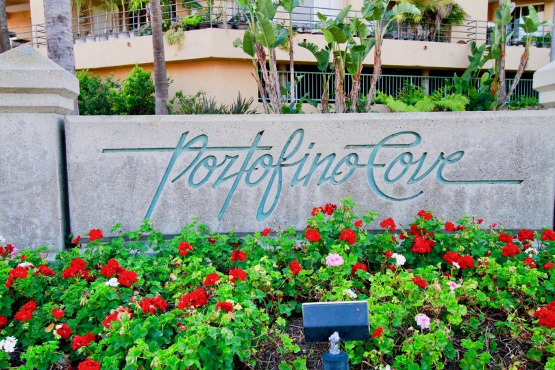 Lovely flower garden with name board with trees near villa of Portofino Cove of Huntington Beach