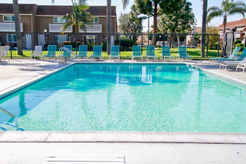 A sunny day by the pool in Huntington Beach with lawn chairs and privacy fence.