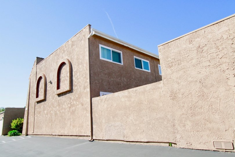 A brown stucco building with a cement parking lot.