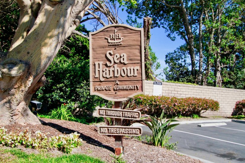 Entrance sign that is tan in color with lots of trees behind in the Sea Harbour community.