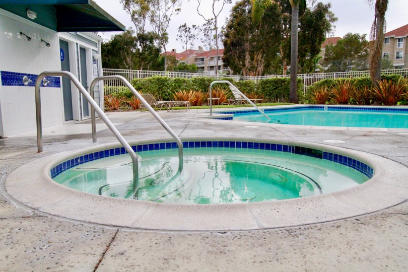 A round hot tub and rectangle pool sit inside the Seabridge Townhomes in Huntington Beach CA
