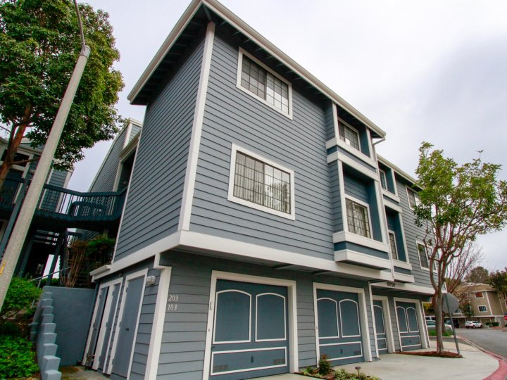 The blue Seabridge Townhomes with bright green tree landscaping and a cement sidewalk entrance.