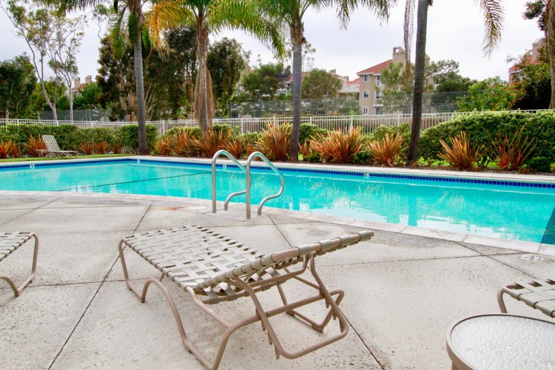 Seabridge Townhomes pool with deck chairs and a table on a cloudy day.