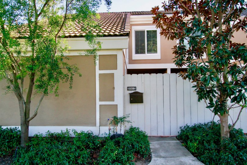 Condo unit with white fence and limited landscaping located in Huntington Beach, CA