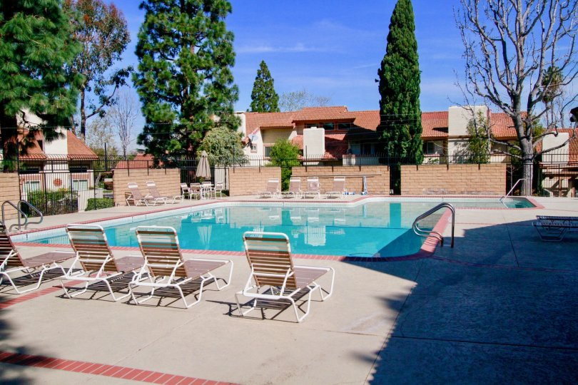 Community pool in residential community located in Huntington Beach California on a sunny day with lounge chairs and no one in the pool