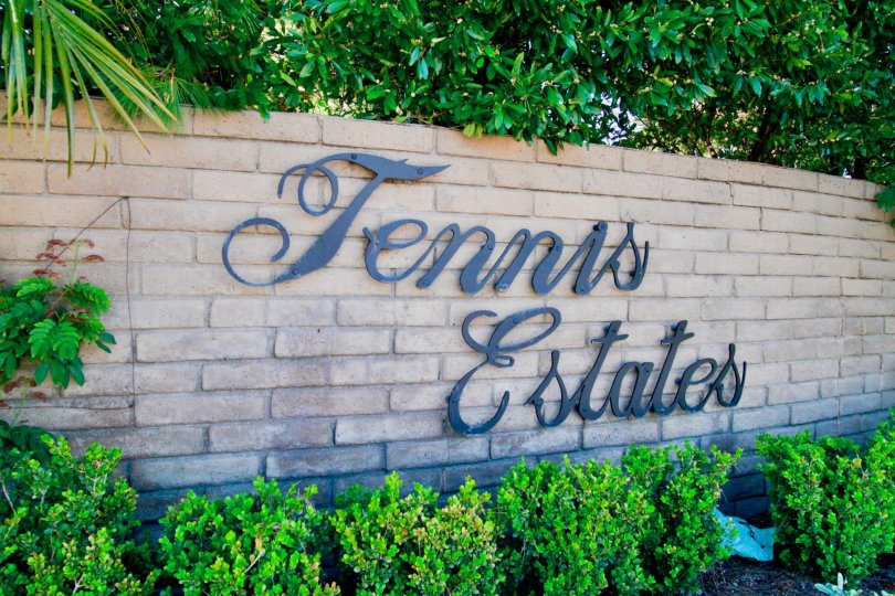 Front sign at Tennis Estates with nice shrubs and plants surrounding the sign.