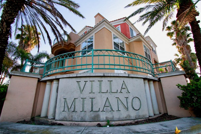 Villa Milano sign with palm trees on either side on a sunny day.
