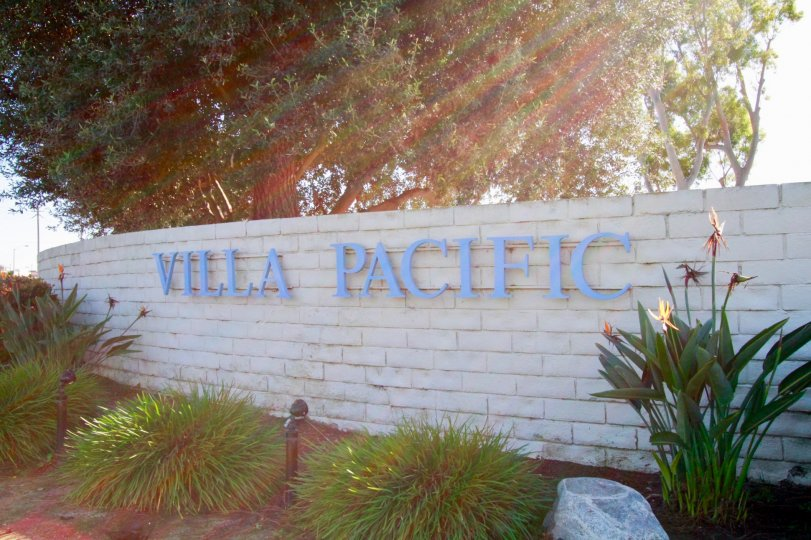 Villa Pacifica stone sign with bushes and trees on a sunny day.