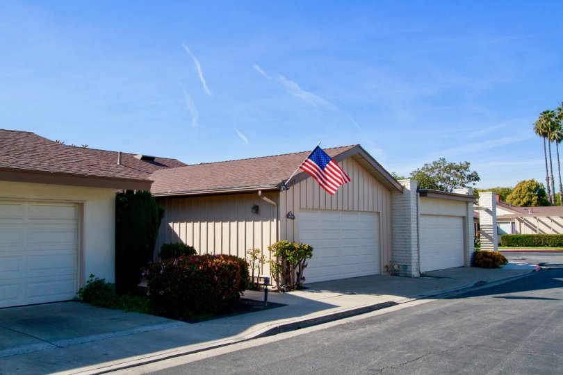 Villa Pacifica homes with a American flag and garages on a sunny day.