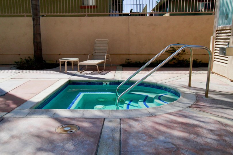 A SWIMMING POOL WITH THE RAMP AND A SITTING CHAIR WITH TABLE ALSO AVAILABLE AND A TREE ALSO NEAR TO THE HOUSE THAT LOCATED NEAR TO THE POOL.
