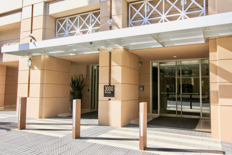 A large glass entryway leading into a large residential building at 3000 The Plaza in Irvine CA