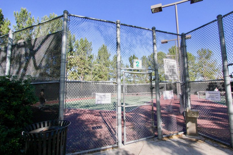 A BRIGHT SUNSHINE AT TENNIS COURTS IN IRVINE, CALIFORNIA WHICH IS SURRONDED WITH STEEL WIRED FENCHING