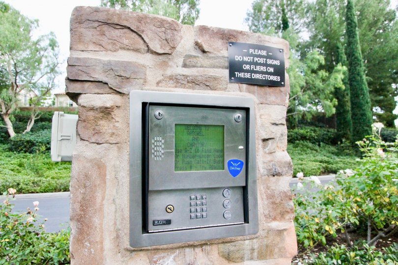 An intercom in Arborel, that is mounted in Sandstone and surrounded by trees.