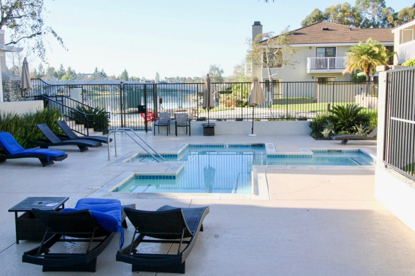 THE HOME IN THE ARBORLAKE WITH THE SWIMMING POOL, CHAIRS, PLANTS, TREES