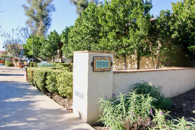 THE ENTRANCE WAY TO THE APARTMENT WHICH IS IN IRVINE, THAT SHOWS THE LOT OF PLANTS, TREES, NAME BOARD ON THE WALL ARE THERE