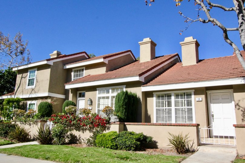 Three town homes with chimneys and front yards inside Cambridge Court in Irvine California