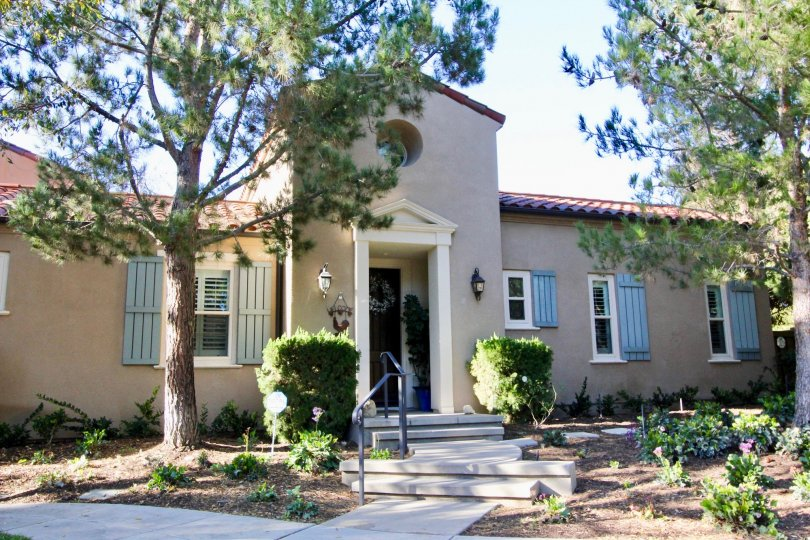 THE FRONT VIEW OF THE HOME WITH TREES, PLANTS, LAMPS ON EACH SIDE ARE SHOWN IN THE CITY OF IRVINE