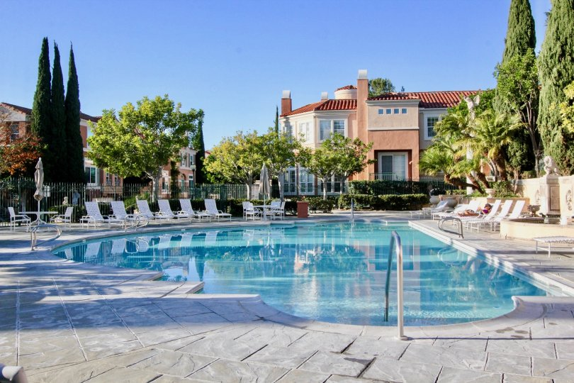 THE SWIMMINGPOOL WITH LOT OF CHAIRS, SURROUNDED BY PLANTS AND TREES, VILLA IS THERE IN THE IRVINE CITY
