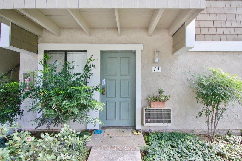 Door step view of the building having plants around in Irvine Springs