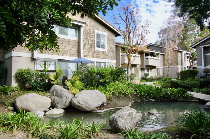 An adorable water filled pond with giant rocks inside Irvine Springs in Irvine California