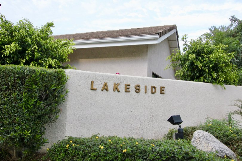 THE OUTSIDE OF THE HOUSE WHICH HAVE THE NAME ON THE WALL, LOT OF PLANTS, TREES ARE THERE IN LAKESIDE COMMUNITY