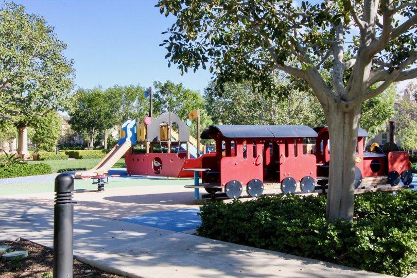 Children's park in Los Arboles has slider, trains with trees