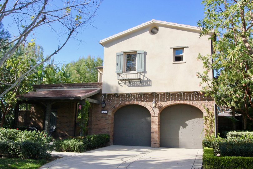 A sunny day in Los Arboles with a large house with plaster and brick finish and a garage