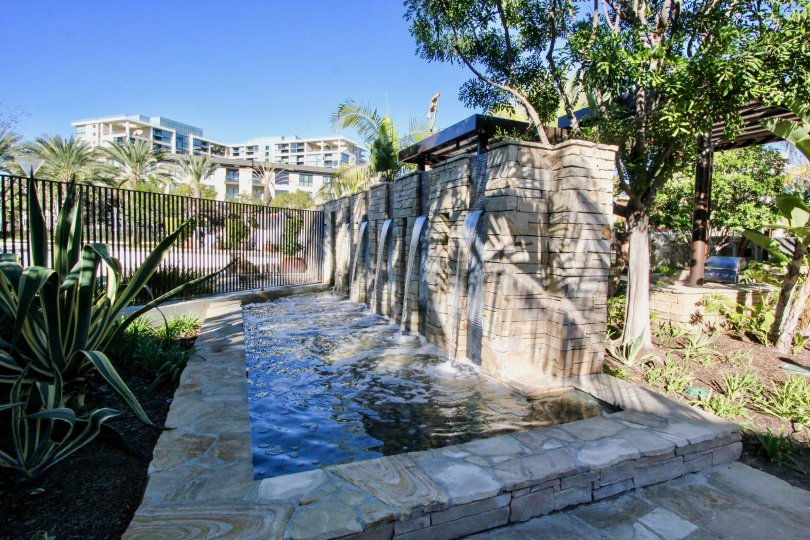 A rock waterfall feature in the Manhattan community in Irvine with the homes in the distance