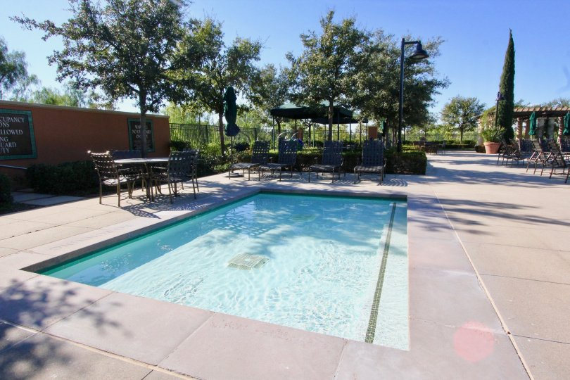 THE SWIMMINGPOOL WITH LOT OF CHAIRS, TABLES, NEARBY PLANTS, AND TREES ARE IN MANZANITA COMMUNITY