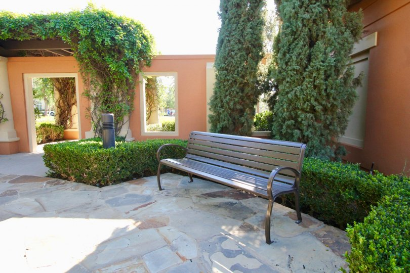 A bench outdoors in a common area in the Manzanita community highlighting the landscaping on a sunny day