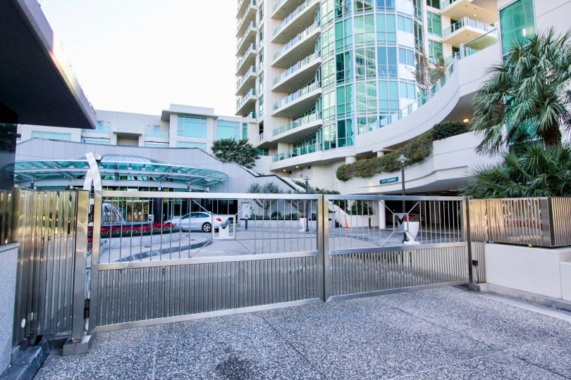 A gated driveway in the Marque at Park Place community with tall buildings.