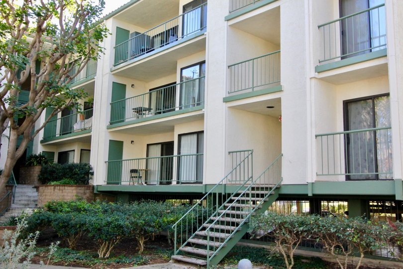 Three story condominium building with attached green stairs inside Orangetree Terrace in Irvine CA