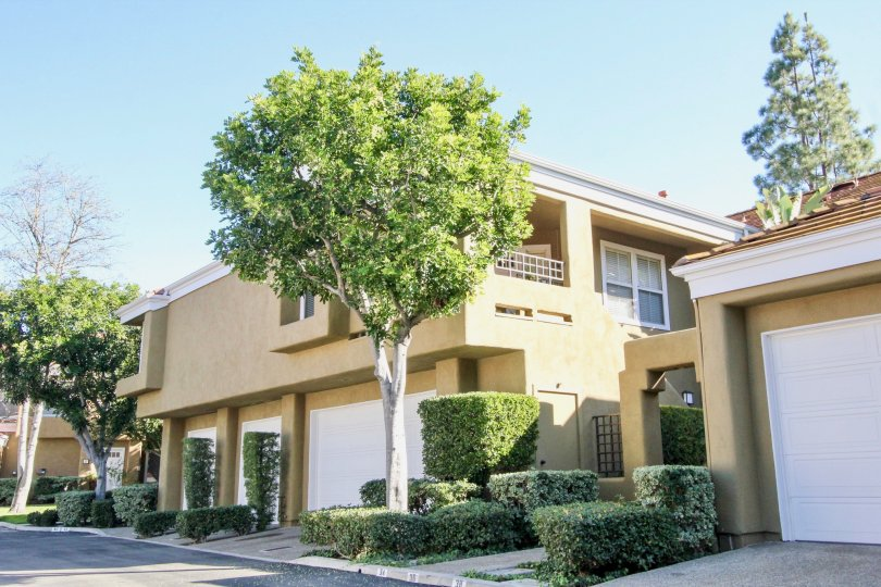 A two story brown painted home with white garage door at Oxford Court in Irvine CA