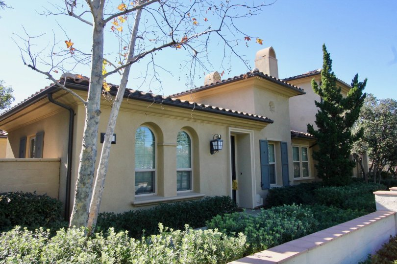 Beige house with tile roof and trees in Paloma, Irvine CA