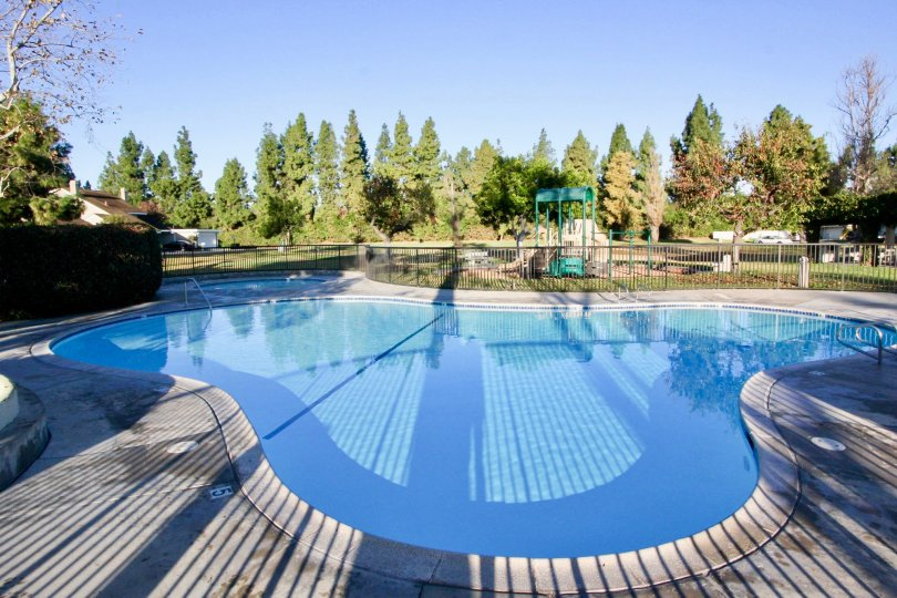 In sunny day of Park Homes with swimming pool with tall trees and meadows