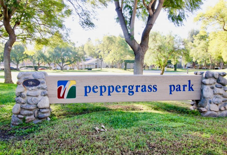 A sunny day at the Peppergrass park sign with trees and grass in the background