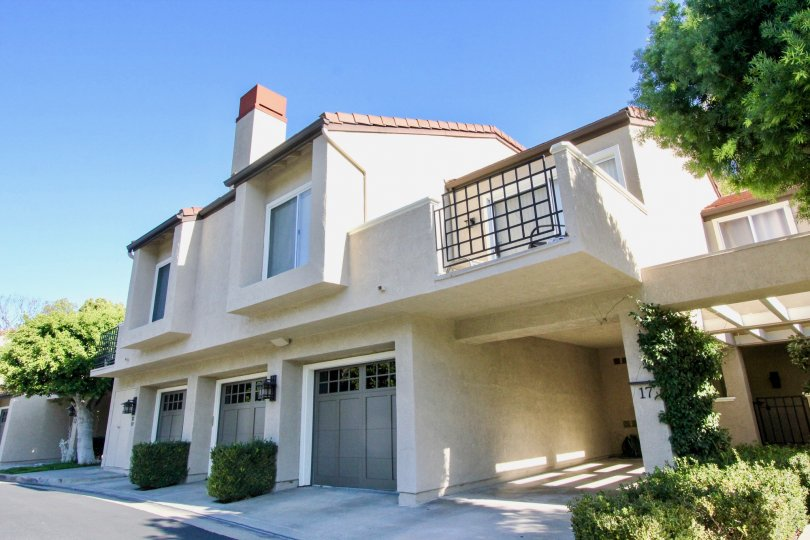 Large three car garage home with lush green landscape and modern exterior. Located in Irvine, CA. Offers a balcony overlooking front side of home.
