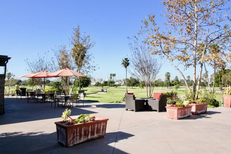 a sunny day at the golf course in the Rancho San Joaquin Townhomes with potted plants and covered tables