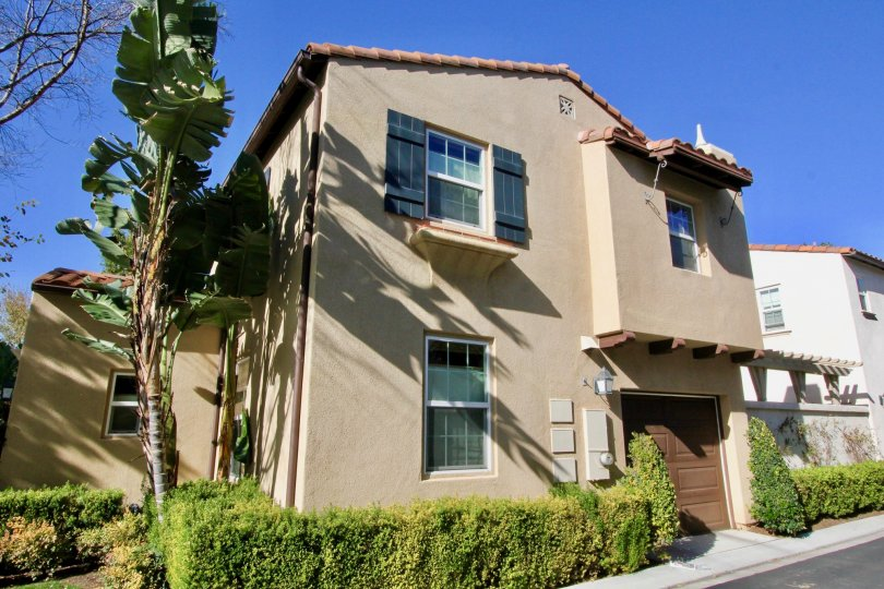 Townhomes with garages and palm trees on a sunny day