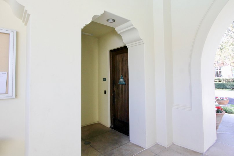 A plain white archway in the Sandalwood community with wooden doors.