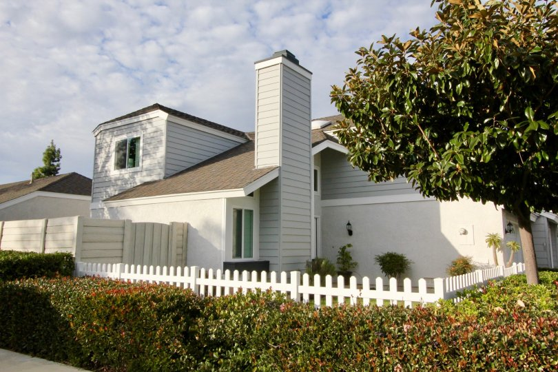 A beautiful house in the seasons of irvine state with a fence and beautiful garden