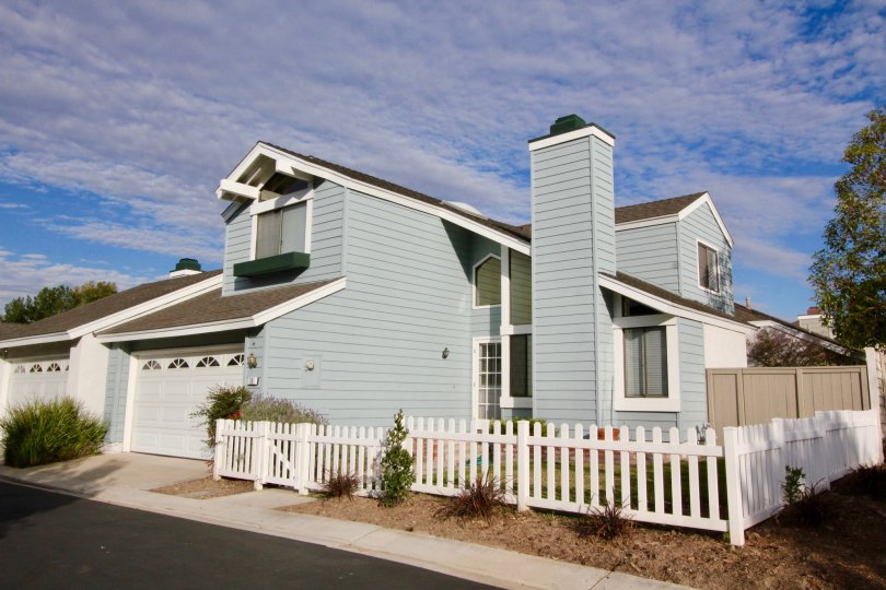 Streetside view of light blue duplex house with small shrubs in Seasons community in Irvine, California