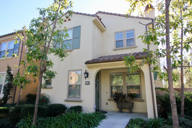 Two story town home with tall trees and a sidewalk at Sendero in Irvine CA