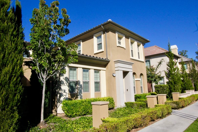A two story brown home with a gray archway entrance inside Stonetree Manor in Irvine CA