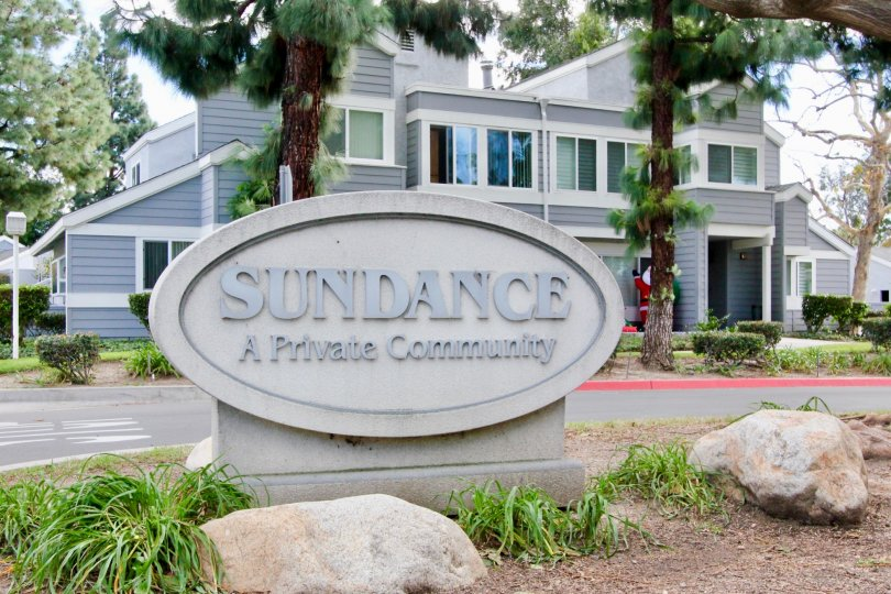 The sign of Sundance community with a home building and trees in the background