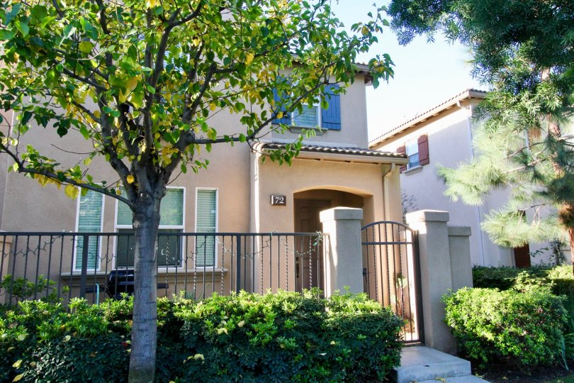 A two story pink home with security gate and archway entrance at Tamarisk in Irvine CA